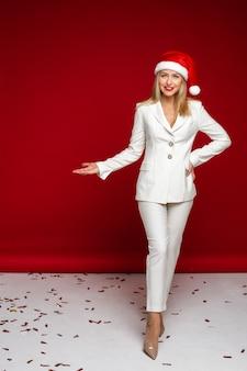 흰색 양복과 산타 모자를 쓰고 그녀의 오른쪽을 가리키는 금발 아가씨의 전체 길이 스튜디오 사진. 휴일 개념
