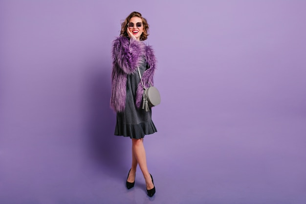 Full-length studio portrait of laughing caucasian girl in elegant black shoes posing on purple background