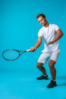 青い背景の上のテニス選手の男の全身スタジオの肖像画をクローズアップ