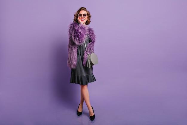 Полнометражный студийный портрет смеющейся кавказской девушки в элегантных черных туфлях, позирующей на фиолетовом фоне
