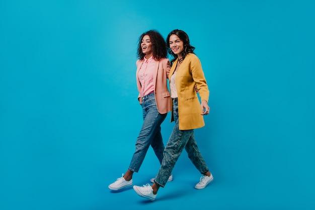 Colpo integrale dello studio di due donne alla moda che camminano sulla parete blu