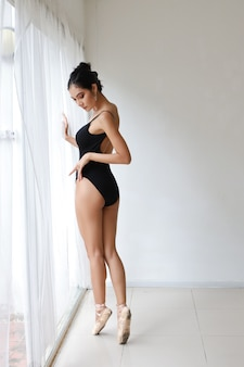 Full length stun shape of charming asian woman in black suit doing ballet dancing on white wall studio
