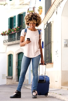 Full length stylish young woman standing with bag and looking at mobile phone
