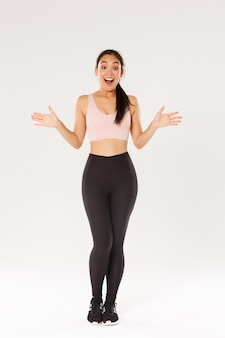 Full length of surprised and amazed female athelte, asian fitness girl in sportsbra and leggings looking wondered, smiling excited and spread hands sideways, find out about gym special discounts.