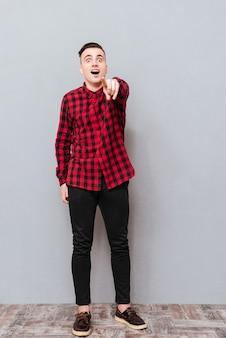 Удивленный хипстер в полный рост в красной рубашке указывает