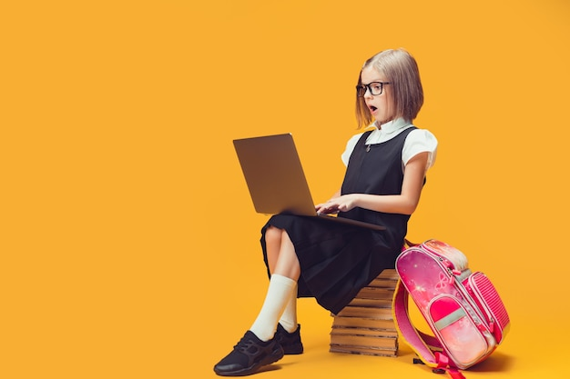 노트북 어린이 교육 개념을 보고 있는 책 더미에 앉아 있는 전체 길이 놀란 학생
