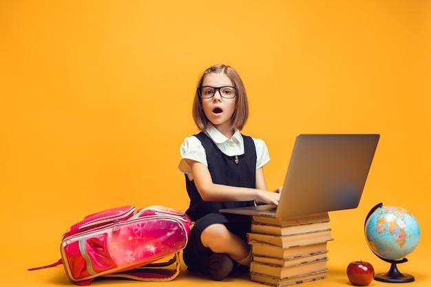 노트북 어린이 교육 개념이 있는 책 더미 뒤에 앉아 있는 전체 길이의 놀란 여학생