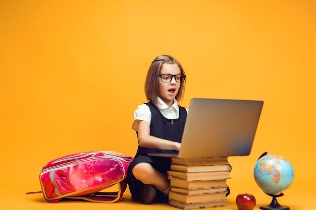 노트북 어린이 교육에 관한 책 더미 뒤에 앉아 있는 전체 길이의 놀란 여학생