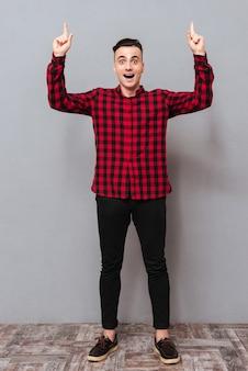 В полный рост удивлен молодой человек в рубашке и черных джинсах, указывая вверх