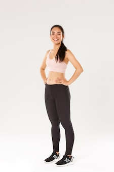 Full length of sweaty smiling fitness girl, female athelte in active wear looking pleased while workout, training in gym, satisfied with exercises, coach helping gain perfect body