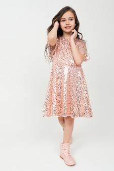 Full-length teenager girl in shiny party dress posing on a white studio background