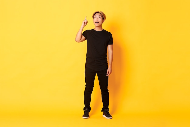 Full-length of thoughtful handsome asian man, raising finger up, have good idea, standing yellow wall