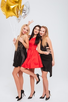Full length of three smiling cute young women holding star shaped balloons and having fun over white background