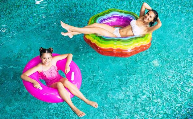 Полнометражное фото сверху, наслаждающиеся загаром, счастливая мать и дочь в бикини на надувных матрасах в бассейне. летний отпуск. отдых в бассейне отеля. семейный отдых