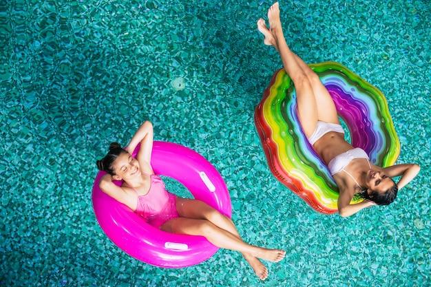 수영장에서 풍선 매트리스에 비키니 입은 선탠, 해피 어머니, 딸의 전체 길이 평면도 사진. 여름 방학. 호텔 수영장에서 휴식을 취하십시오. 가족 휴식
