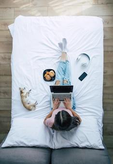 Полнометражное фото вид сверху молодой брюнетки в повседневной одежде, пока она работает с ноутбуком в постели. счастливая девушка учится с собакой дома