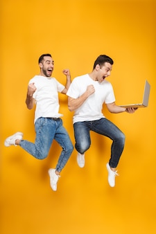 Full length of two cheerful excited men friends wearing blank t-shirts jumping isolated over yellow wall, using laptop, holding credit card