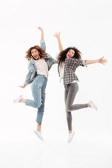 Full length two joyful girls rejoices and jumping  over white wall