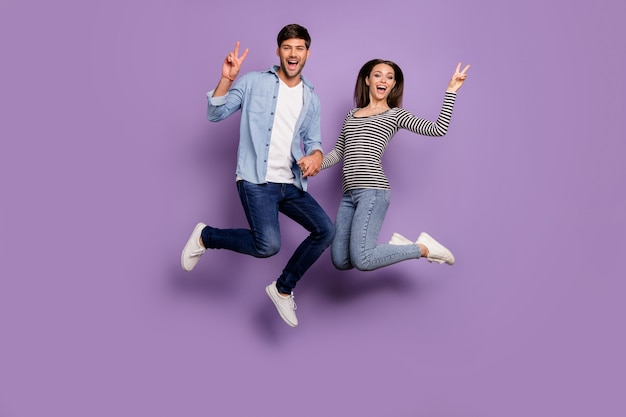 Full length  of two people couple funny guy lady jumping high holding hands showing v-sign symbols wear stylish casual clothes isolated pastel purple color wall