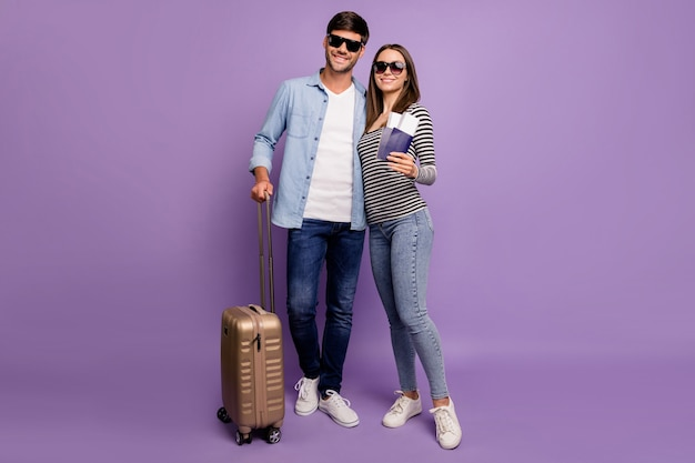 Full length two people couple guy lady walking airport registration tickets passports baggage vacation time wear stylish casual clothes isolated pastel purple color wall