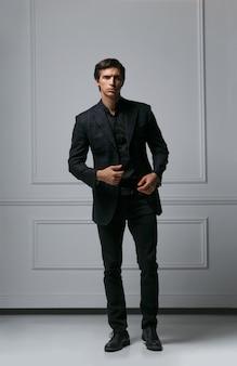 Полнометражное вертикальное изображение элегантного модного мужчины, регулирующего свой костюм, глядя в камеру, позирует в студии возле стены в неоклассическом стиле.