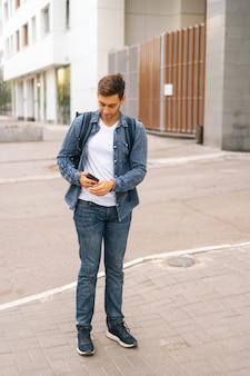 도시 거리에 있는 전화에 탐색 앱을 사용하여 보온 배낭을 메고 잘생긴 남성 택배사의 전체 길이 세로 초상화. 스마트폰을 찾고 클라이언트 주소를 검색하는 배달 남자.