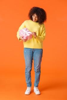 전체 길이 세로 샷 귀엽고 생일 축하 소녀 unwrapping 선물, 스웨터에 곱슬 머리를 가진 아프리카 계 미국인 여자 미소, 핑크 선물 호기심 안에 오렌지 벽을 들고.