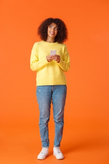 전체 길이 세로 샷 꿈꾸는 귀여운 아프리카 계 미국인 여자가 무엇을 쓸지 생각하고, 스마트 폰을 들고 생각하고 이미지 물건을 웃고 서서 오렌지 벽을 즐겁게합니다.