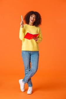 Lo scatto verticale a figura intera ha trovato una soluzione, pensa alla risposta come studiare, prendere appunti durante la lezione. la studentessa afroamericana attraente scrive in taccuino e sorridendo ha avuto un'idea, diciamo eureka.
