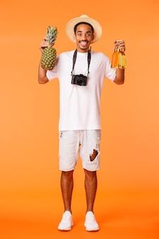 Colpo verticale a figura intera felice ragazzo afroamericano che suggerisce di prendere un drink e godersi le vacanze, tenendo in mano ananas e due bottiglie di birra, sorridendo entusiasta, rilassandosi nel tempo libero, sfondo arancione