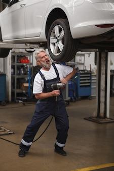 Полноразмерный вертикальный снимок старшего бородатого работника автосервиса, весело позирующего с поднятым автомобилем в гараже