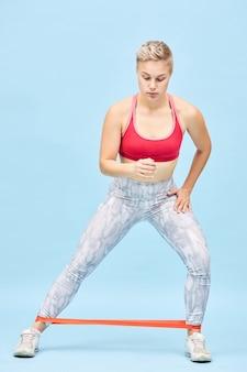 Colpo verticale a figura intera di ragazza atletica autodeterminata che fa allenamento cardio eseguendo passaggi laterali in piedi o passeggiate utilizzando la fascia di resistenza per allenare glutei, muscoli posteriori della coscia, polpacci e quadricipiti