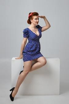 大きな胸と生姜の髪が快適に座って、額に手をつないで、遠くに何かを見ようとしているファッショナブルな魅力的な若いヨーロッパの女性の全身垂直図