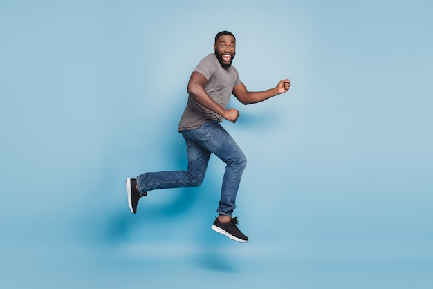 Full length view of afro guy jumping running isolated on blue background