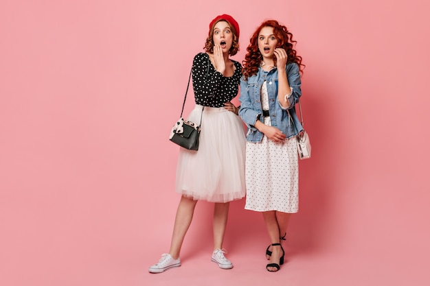 Full length view of amazed girls looking at camera with open mouth. studio shot of female friends expressing surprised emotions.
