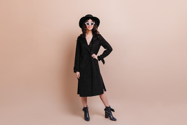 Full length view of asian woman in black coat. studio shot of confident korean woman standing on beige background.