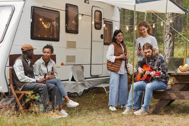 秋のコピースペースでキャンピングカーで屋外でリラックスする若者のグループでの完全な長さのビュー