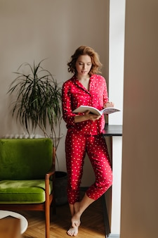 Full length view of barefoot lady reading magazing with interest. indoor shot of pleased woman in red sleepwear in living room.