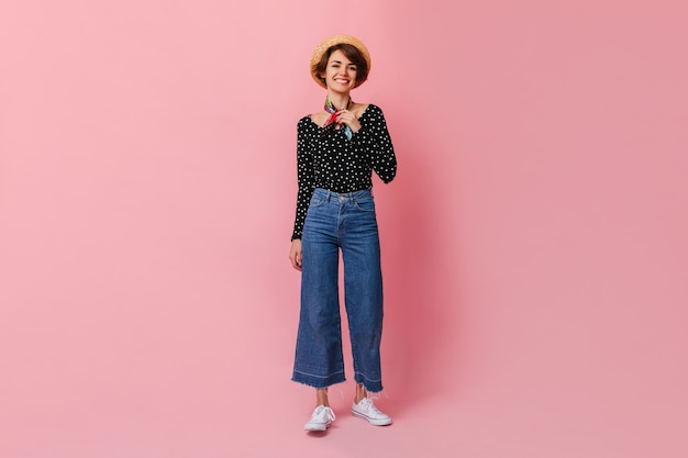 Full length view of charming woman in vintage jeans