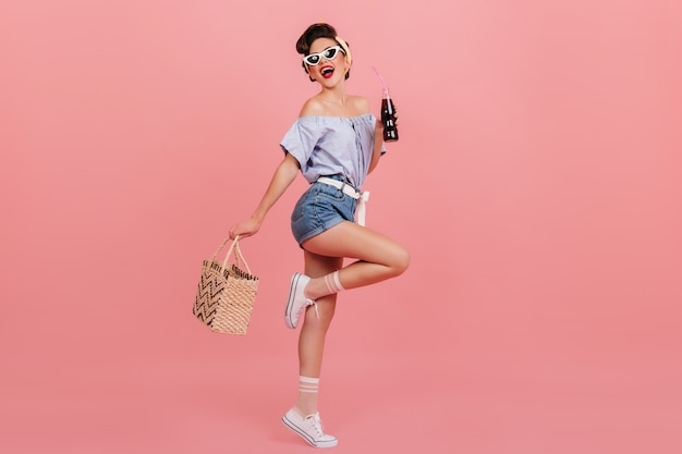 Vista integrale della ragazza pinup ballante. studio shot di graziosa giovane donna con una bottiglia di bevanda e borsa.