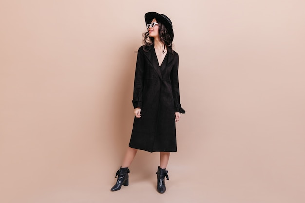 Full length view of dreamy brunette woman in sunglasses and coat. gorgeous stylish woman in hat standing on beige background.