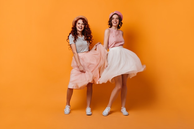 Full length view of enthusiastic girls with curly hair dancing with smile. studio shot of glad female friends having fun on yellow background.