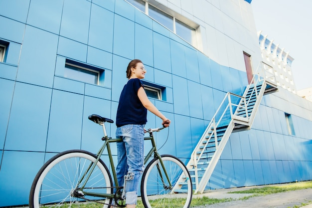 Full length view of fashionable girl in denim and t-shirt standing with bike against the blue wall building. leisure concept.