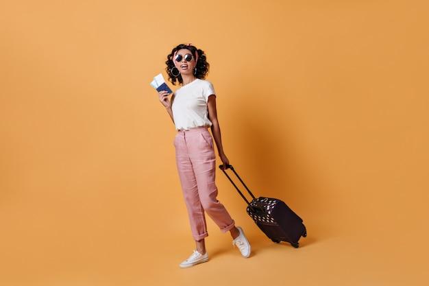Full length view of female traveler in sunglasses