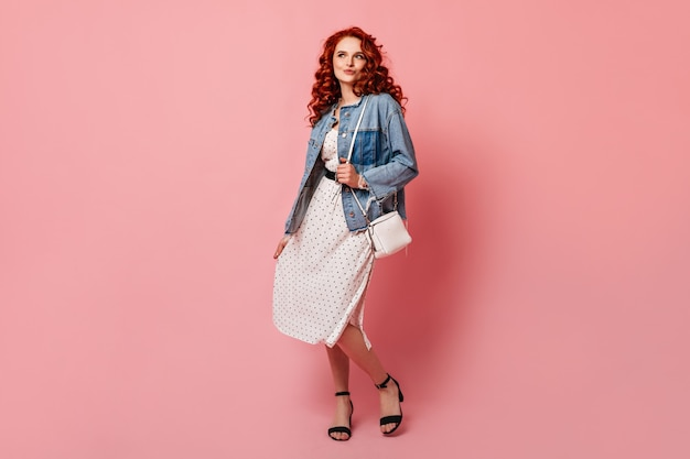 Full length view of ginger woman dancing on pink background. studio shot of curly girl in denim jacket looking at camera.