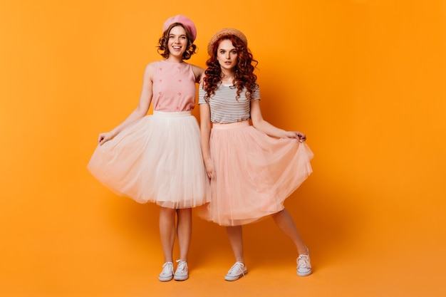 Full length view of girls playing with skirts. studio shot of glamorous female friends standing on yellow background.