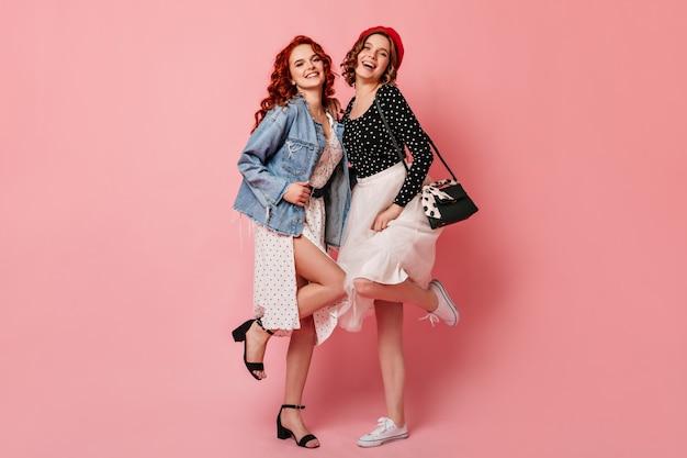 Vista integrale di ragazze graziose che ballano con il sorriso. studio shot di amici in abbigliamento casual.