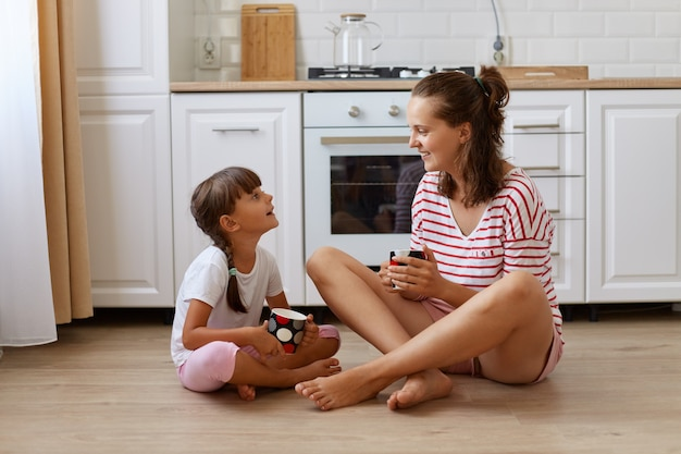 Full length view of happy mother drinking tea in cup with her smiling daughter, sitting on kitchen floor, having breakfast and spending weekend together at home.