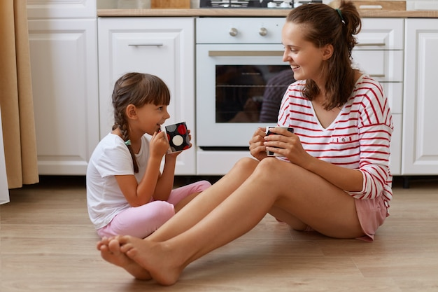 Full length view of happy mother drinking tea from cups with her smiling daughter, family sitting on kitchen floor, having breakfast and spending weekend together at home