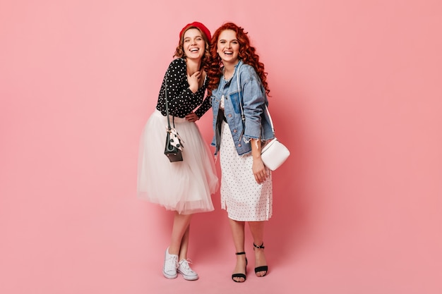 Full length view of happy sisters laughing at camera. studio shot of trendy girls posing on pink background with smile.